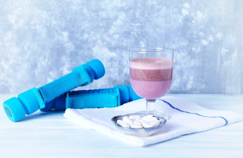 Verre de secousse de protéine de chocolat avec du lait et le cassis L - Carnitine et haltères bleues à l'arrière-plan images libres de droits