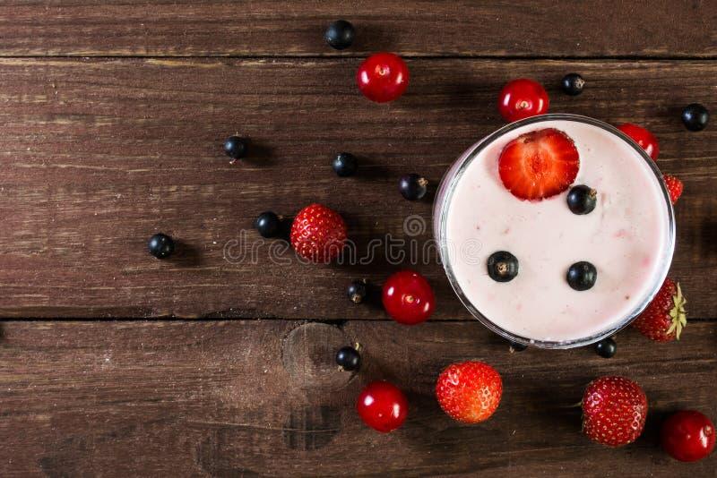 Verre de smoothie de yaourt de baie sur la table en bois photographie stock libre de droits
