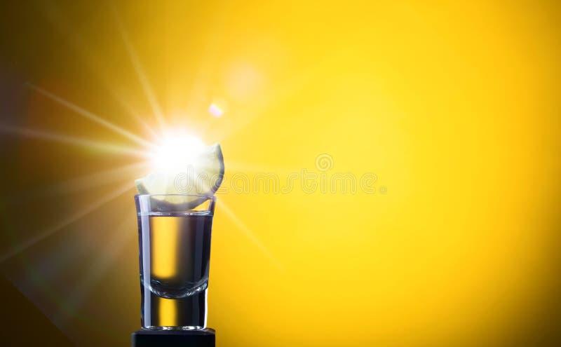 Verre de tequila avec la chaux sur un fond jaune image libre de droits