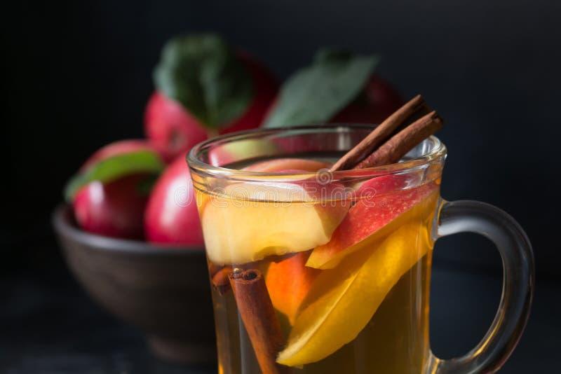 Verre de thé avec la pomme et la cannelle de citron, épicée, coupé en tranches sur le conseil noir D'automne toujours durée image libre de droits