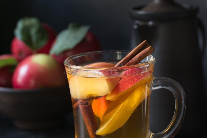 Verre de thé avec la pomme et la cannelle de citron, épicée, coupé en tranches sur le conseil noir D'automne toujours durée photo libre de droits