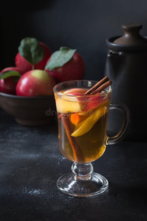 Verre de thé avec la pomme et la cannelle de citron, épicée, coupé en tranches sur le conseil noir D'automne toujours durée images libres de droits