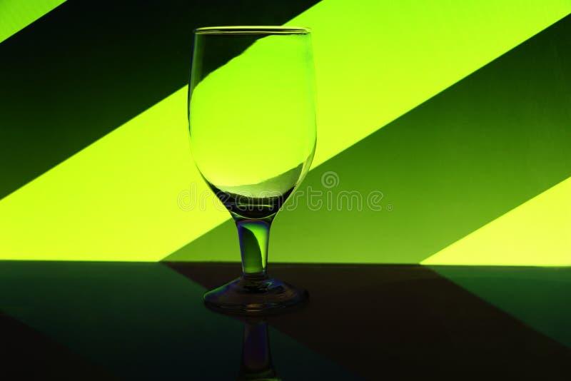 Verre de vin à l'arrière-plan coloré vert clair et vert-foncé image stock