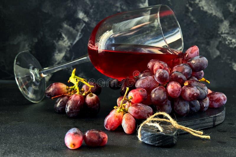 Verre de vin avec des raisins sur un support en bois noir photos libres de droits