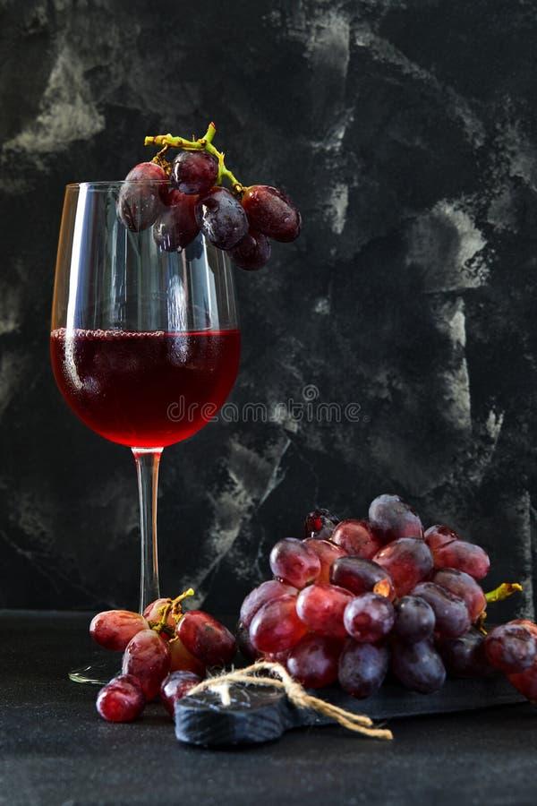 Verre de vin avec des raisins sur un support en bois noir images stock