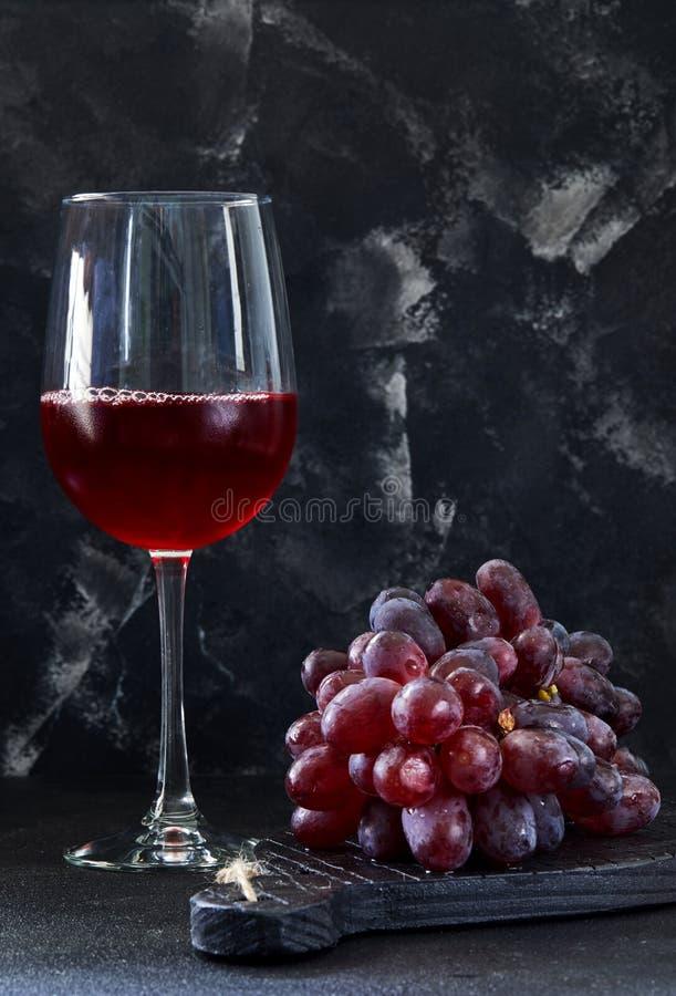 Verre de vin avec des raisins sur un support en bois noir image libre de droits