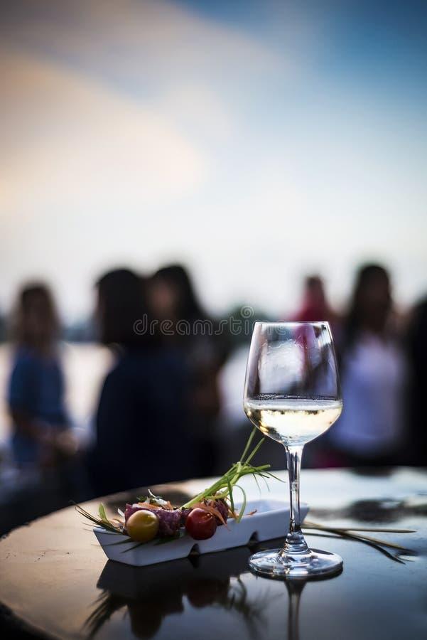 Verre de vin blanc avec des casse-croûte de tapa de Plats gastronomiques dehors photographie stock