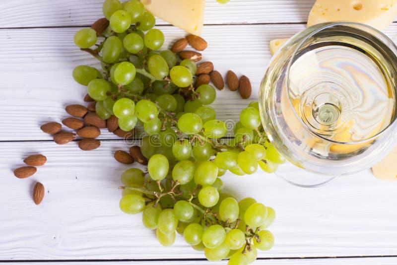 Verre de vin blanc avec les casse-croûte - divers types de fromage, figues, écrous, miel, raisins sur un fond de conseils en bois photo stock