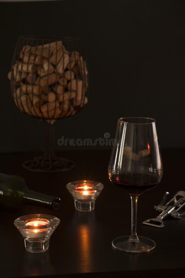 Verre de vin dans le premier plan avec une bouteille vide, un tire-bouchon et des lièges des bouteilles à l'intérieur d'un vase s images libres de droits