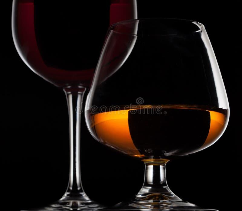 Verre de vin et verre de whiskey sur le fond noir photo libre de droits