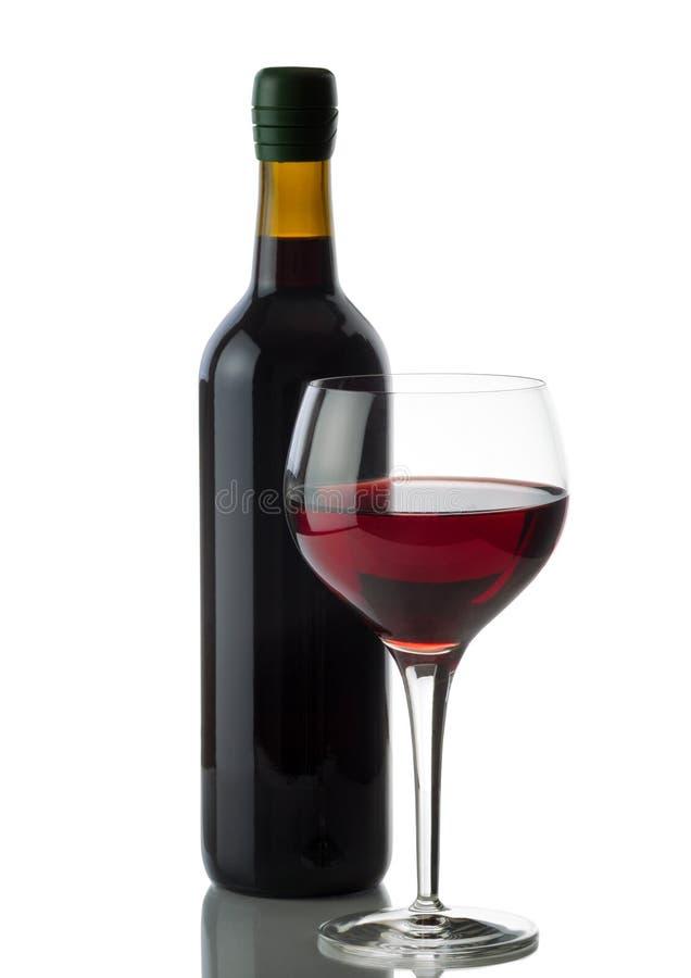 Verre de vin rouge avec la pleine bouteille sur le fond blanc photographie stock