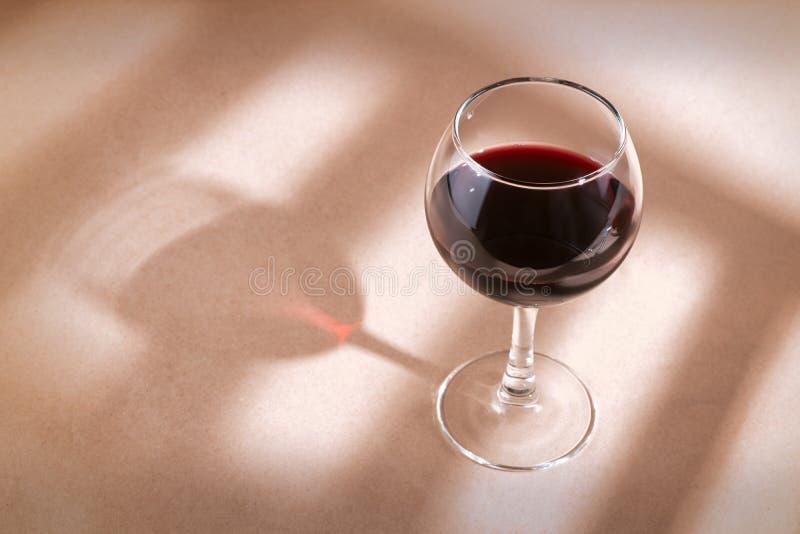 Verre de vin rouge sur la table avec l'ombre de fenêtre photos stock