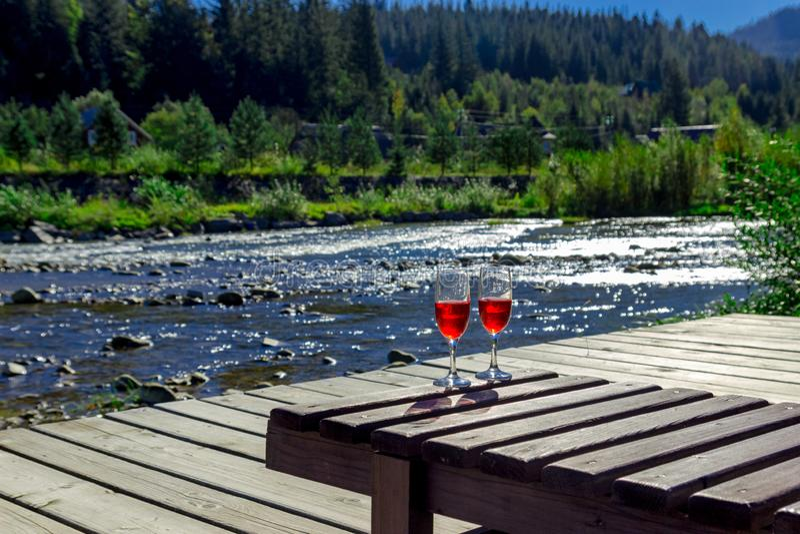Verre de vin rouge sur le fond d'une rivière de montagne Salon en bois de cabriolet, montagnes, vacances de luxe image libre de droits