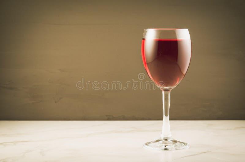 verre de vin rouge sur un fond brun/un verre vin rouge sur un fond brun Foyer s?lectif et copyspace photo stock