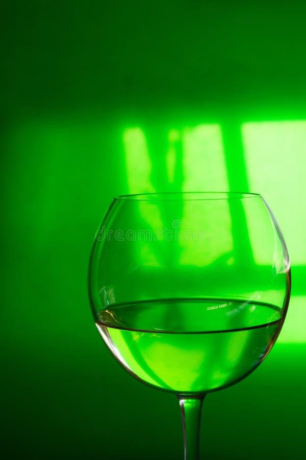 Verre de vin sec blanc transparent sur le fond translucide vert avec les ombres dures de réflexion de fenêtre Créatif conceptuel images libres de droits