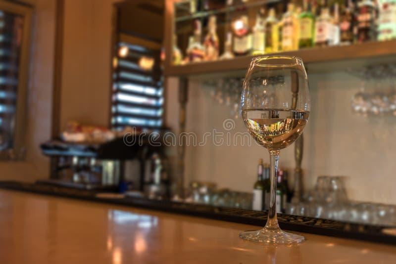 Verre de vin sur le compteur de barre dans le bar ou le restaurant Fond brouillé lumineux avec une machine et des verres de café  images libres de droits