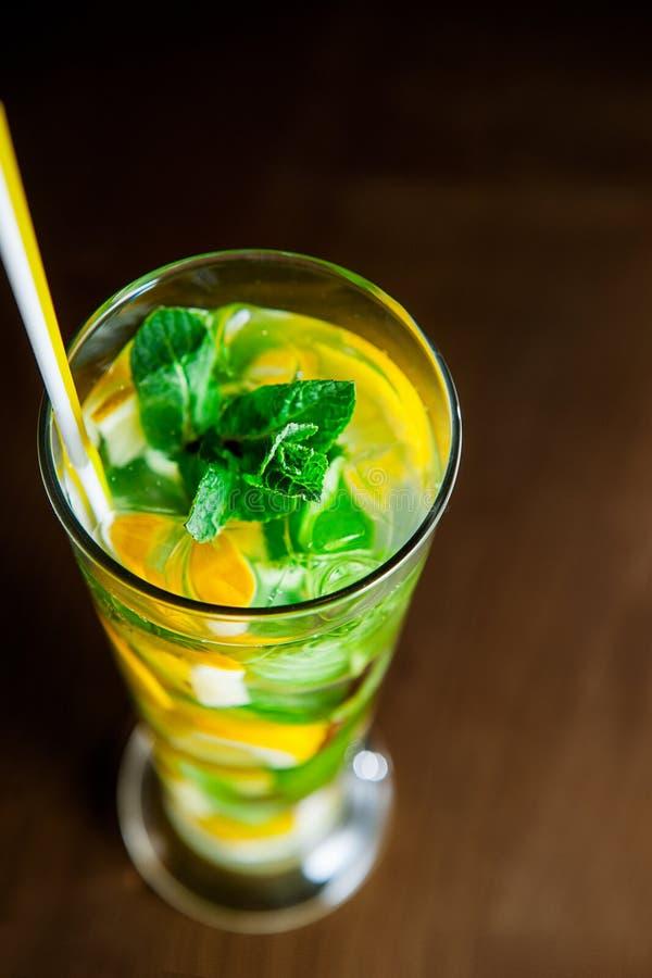 Verre de vue supérieure de limonade avec des cales de menthe et de citron sur le fond en bois foncé Foyer sélectif image stock