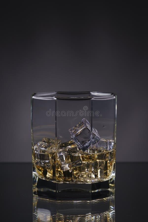 Verre de whiskey avec de la glace sur un fond gris photographie stock