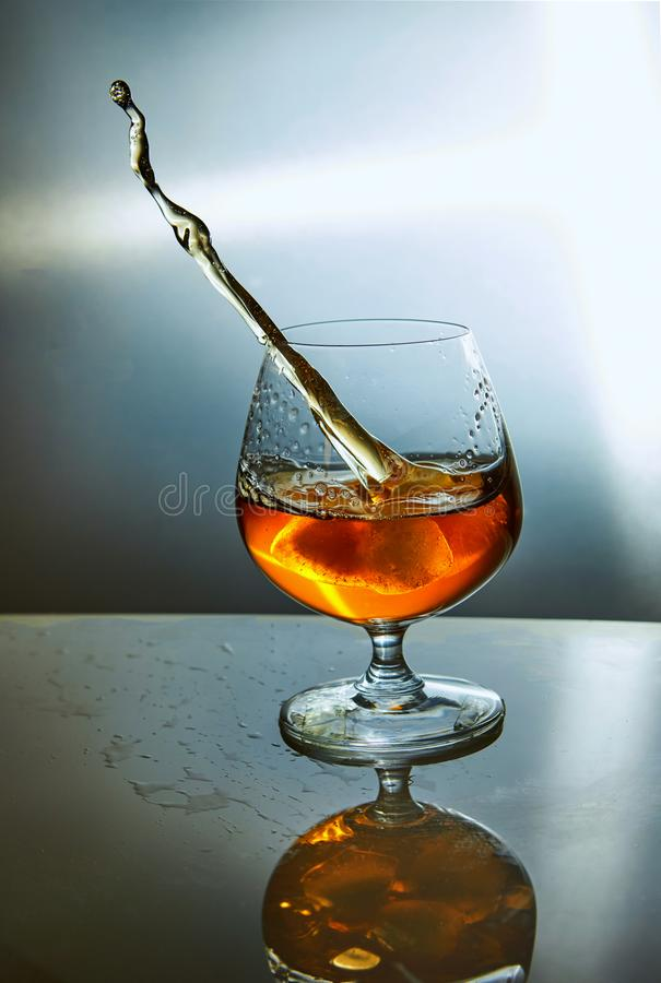Verre de whiskey avec une vague sur un fond bleu photos stock