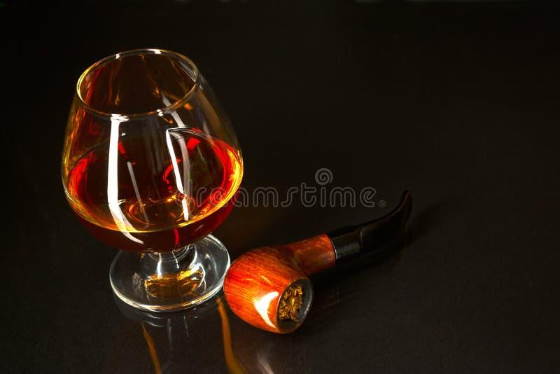 Verre de whiskey et tuyau de tabagisme sur le fond noir photos stock