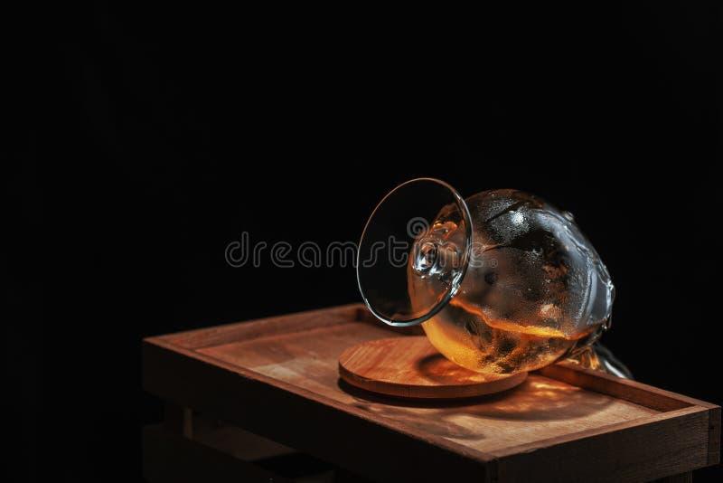 Verre de whiskey retourné et absorbé de la glace froide de laquelle suit la boisson, sur un appui en bois sur un fond noir photo libre de droits