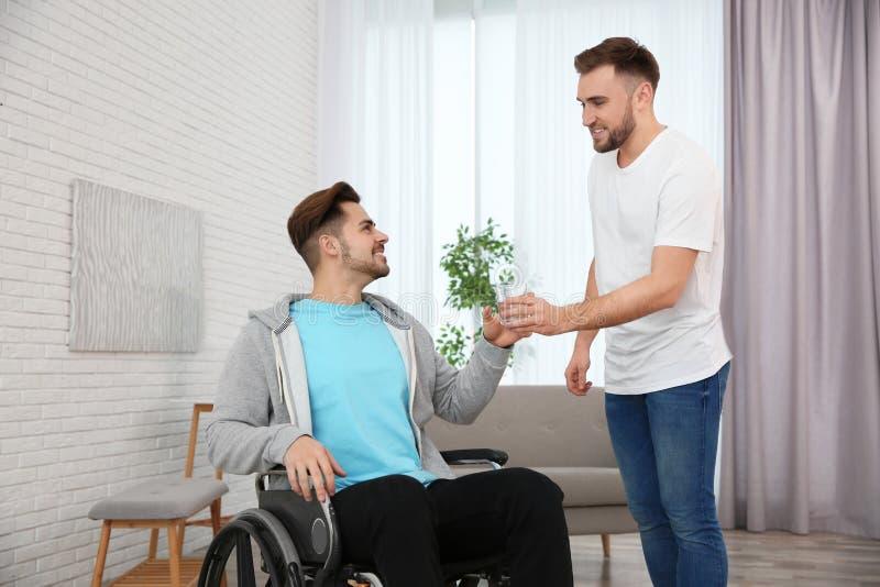 Verre donnant volontaire de l'eau à équiper dans le fauteuil roulant Aide handicap?e photographie stock