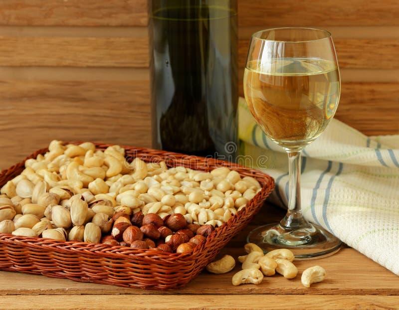 Verre du vin blanc, des écrous et de la serviette de toile photographie stock libre de droits