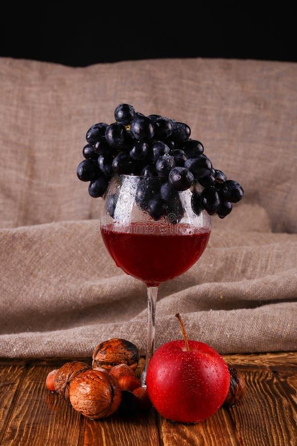 Verre du vin rouge et du raisin au-dessus du noir photos stock