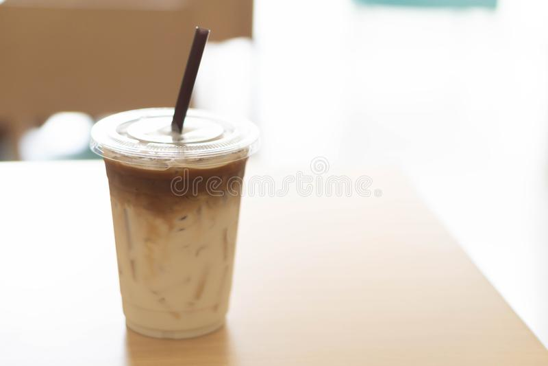 Verre en plastique de plan rapproché de café de glace sur la table en bois avec le ligh fini photos stock