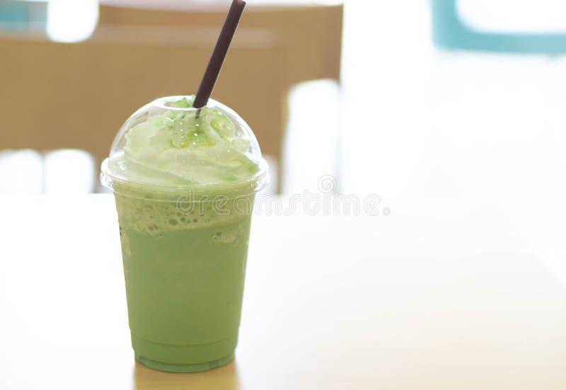 Verre en plastique de plan rapproché de milk-shake de matcha de glace sur la table en bois avec l'OV image stock