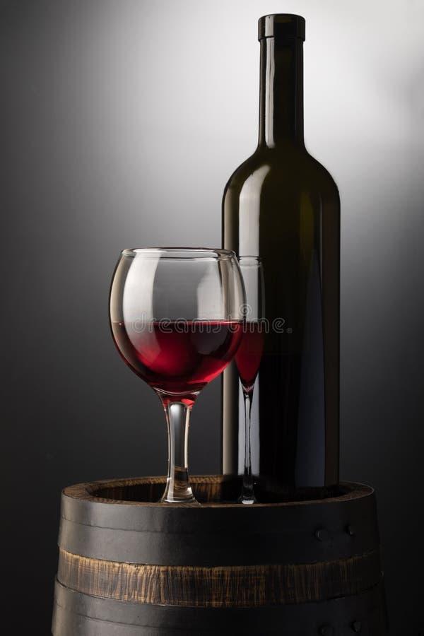 Verre et bouteille de vin rouge sur le vieux baril en bois photographie stock