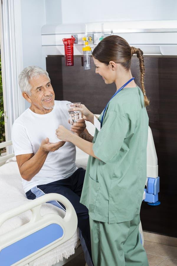 Verre et médecine d'eau patients de réception d'infirmière féminine photos libres de droits
