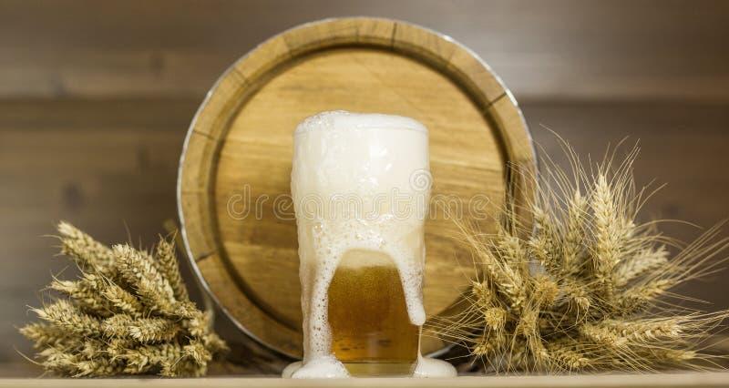 Verre et mousse de bière à l'arrière-plan du blé de barils image libre de droits