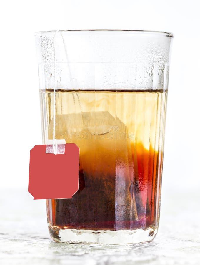 Verre facetté de l'eau et de sachet à thé bouillis photos libres de droits