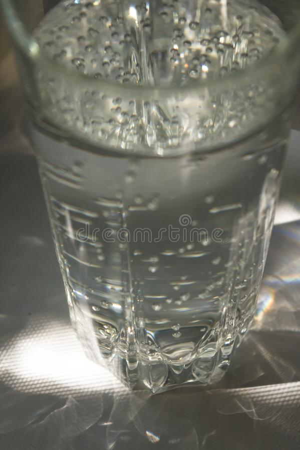 verre facetté transparent avec de l'eau pétillant photos stock
