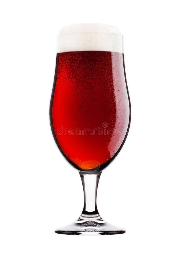 Verre froid de bière amère rouge avec la mousse et la rosée image stock