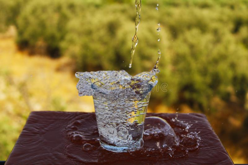 Verre gentil de l'eau étant remplie photographie stock libre de droits