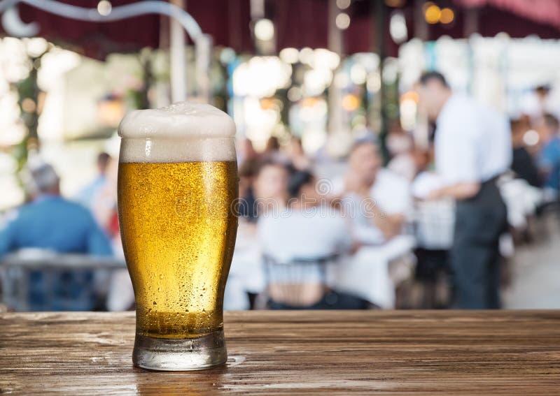 Verre givré de bière blonde sur le café de compteur de barre en plein air photos stock