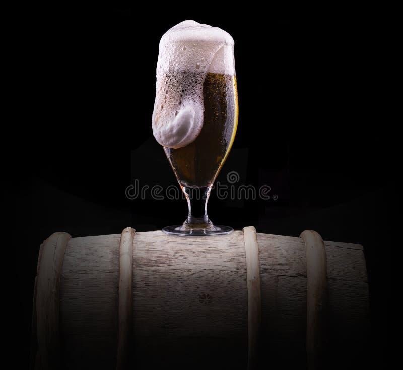 Verre givré de bière blonde sur le fond noir image stock