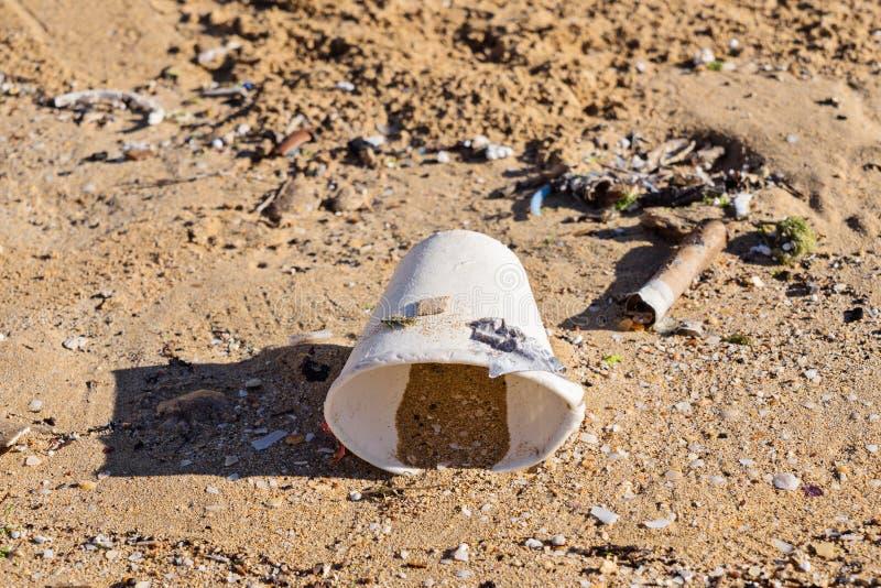 Verre jetable de vaisselle sur la plage sablonneuse après marée photo libre de droits