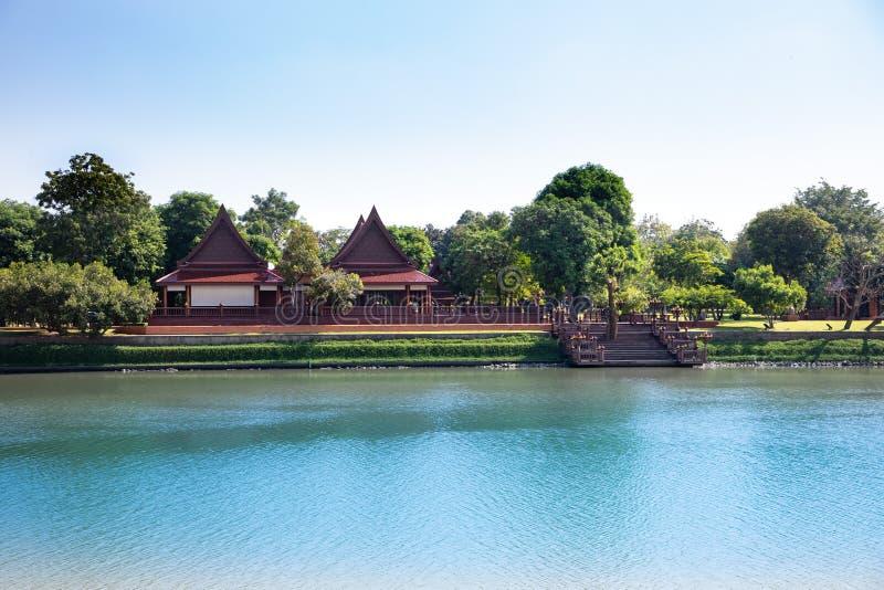 Verre mening van een typisch landschap van Thailand met een blauwe rivier en tempeldaken en groene bomen op de achtergrond royalty-vrije stock fotografie
