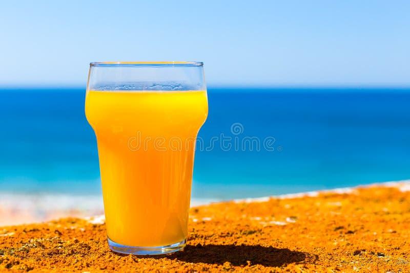 Verre rempli de jus d'orange en mer photos libres de droits