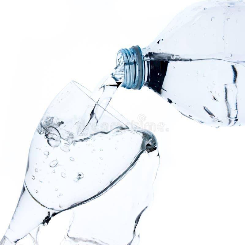 Verre remplissant avec de l'eau de bouteille en plastique photographie stock