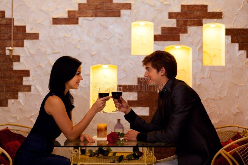 Verre romantique de boissons de date de jeunes couples heureux de photo libre de droits