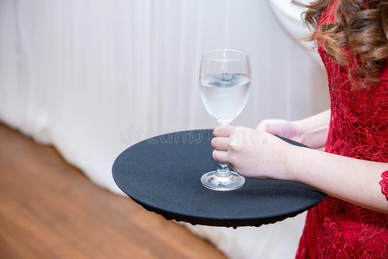 verre rouge de champagne de prise de robe d'usage attrayant de fille sur sa main et plat noir image stock