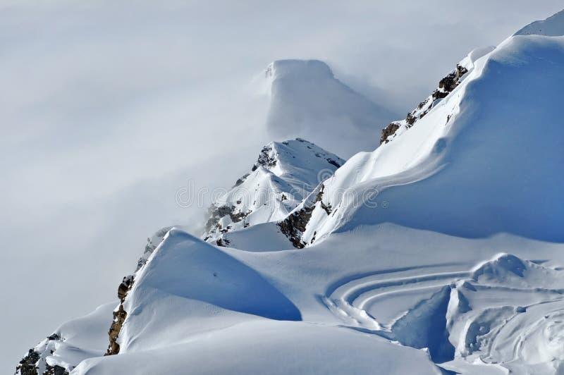 Verre sneeuw behandelde pieken boven wolken stock foto