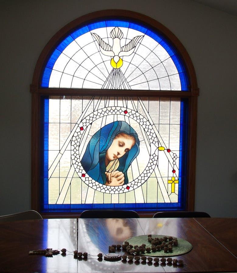 Verre souillé béni de Vierge Marie avec la réflexion et le chapelet image stock