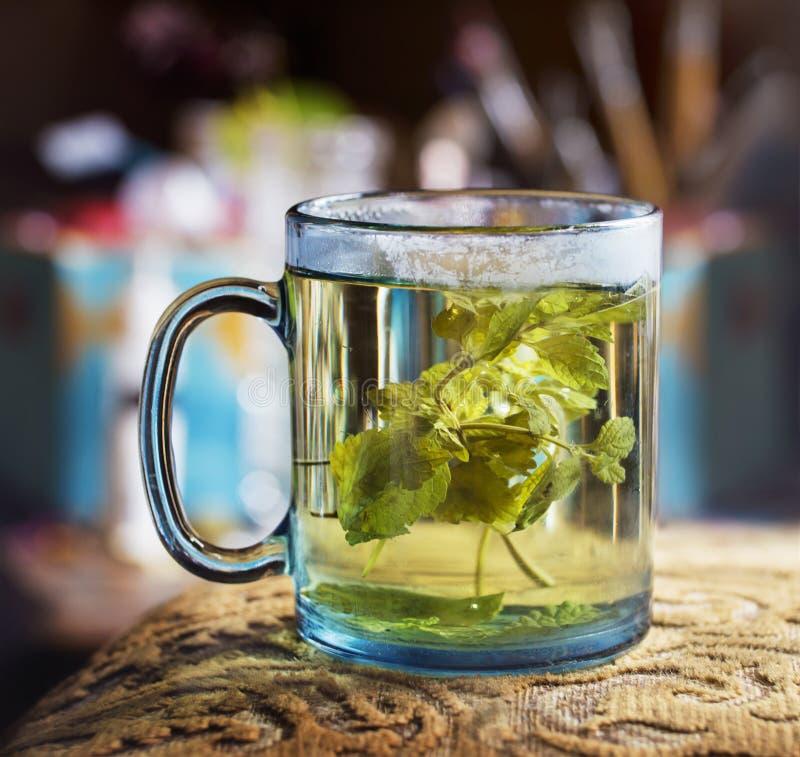 Verre transparent bleu de thé chaud avec le baume de citron photographie stock libre de droits
