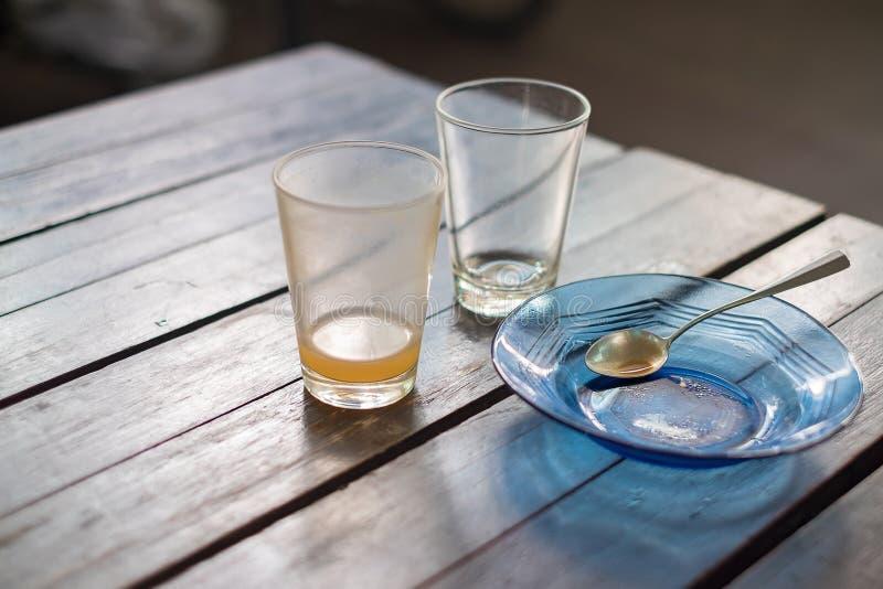 Verre vide de thé chaud dedans avec la soucoupe et la cuillère sur la table en bois, photo stock