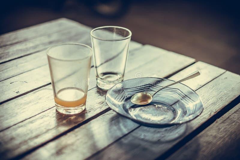 Verre vide de thé chaud dedans avec la soucoupe et la cuillère sur la table en bois images stock